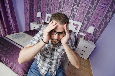 Man with hangover and funny expression in vintage home bedroom photo