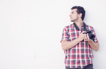 supported: Casual photographer tired supported on a wall Stock Photo