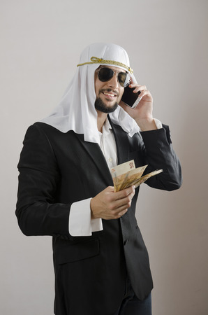 bohra: The arab man businessman with money, suit and phone cliche Stock Photo