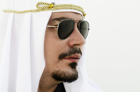 25 30 years: Arab man profile with sun glasses on white wall