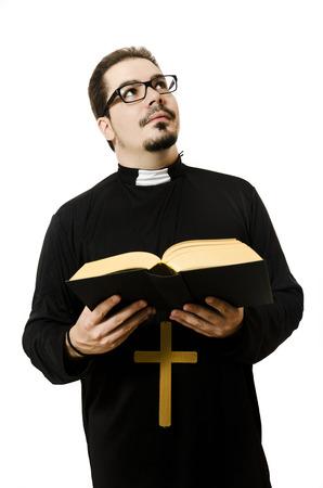 sotana: Sacerdote leyendo el bibble y buscar. Aislado en el fondo blanco.