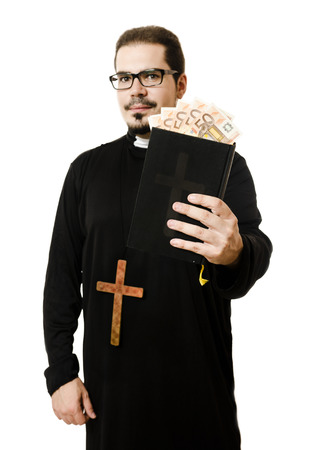 Priest holding bible with euro currency in pages. Symbol of religion and money. Focus in bills. Stock Photo