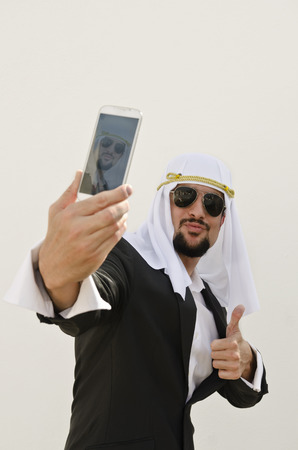 suriyah: Arab man taking selfie with smart phone in outdoors white wall
