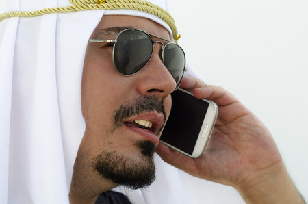 riches adult: Arab man close up image calling with smart phone