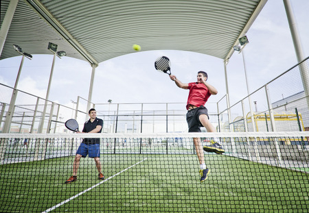 tennis net: Two men playing paddle tennis in wide angle shot image Stock Photo