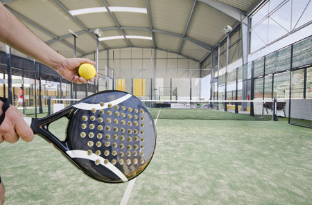 Paddle tennis serve at indoor court in wide angle image