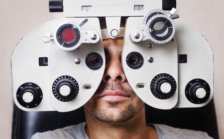astigmatism: Man in optometrist phoropter redy for eye exam calibration