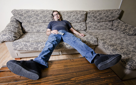 man couch: Adult man resting in sofa like a couch potato with remote control on belly
