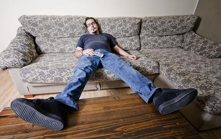 perezoso: Hombre adulto descansando en el sofá como un adicto a la televisión con mando a distancia en el vientre Foto de archivo
