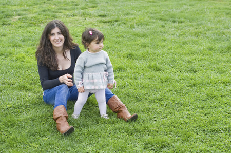 two people with others: Mother and daughter in outdoors park on the grass.