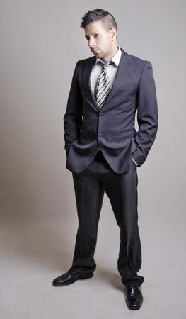 gray suit: Young suit man posing in studio shot full length portrait