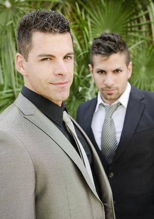 hombres gays: Dos hombres de traje elegante joven posando en el jardín al aire libre mirando la vista, la luz natural.
