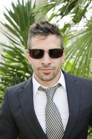 hombres gays: Traje hombre joven posando con gafas de sol en el jardín al aire libre
