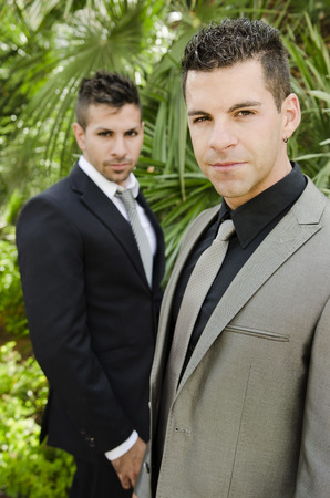 Two suit young elegant men posing in outdoors garden looking at the view, natural light. photo