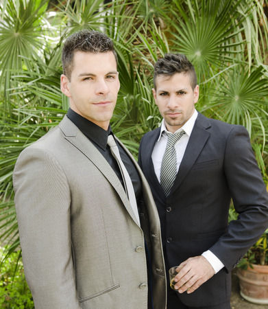 dark haired: Two suit young elegant men posing in outdoors garden looking at the view, natural light.