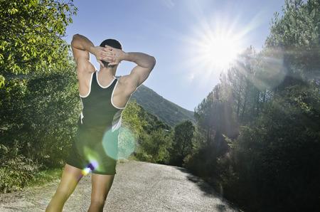 warm up: Runner uomo di riscaldamento armi con la luce del sole effetto riflesso nello all'aperto, riscaldamento e stretching