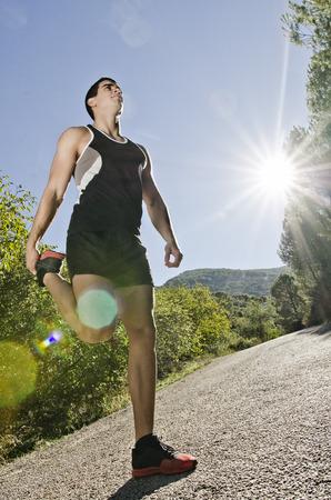 warm up: Runner riscaldamento uomo gambe con la luce del sole effetto riflesso in esterna, si riscaldano e si estende su strada.
