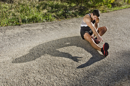 warm up: Runner man warming arms with sun light shadow, warm up and stretching Stock Photo
