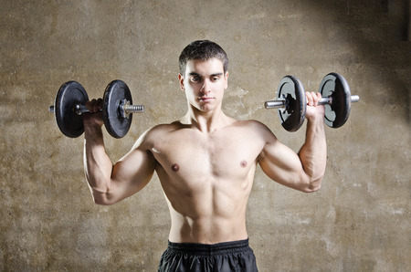 Young brunette man training shouder muscles exercises in old gym photo