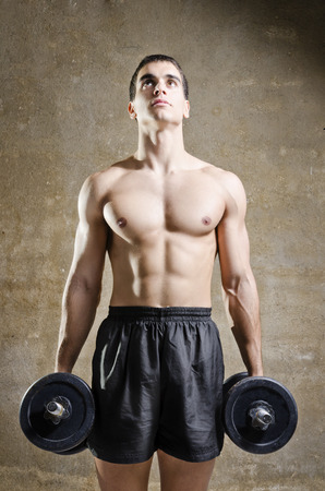 Young brunette man training shoulder muscles exercises in old gym photo