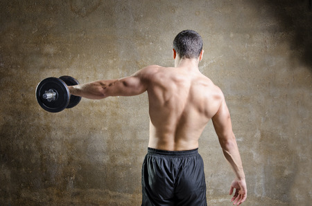 Young man  training shouder and back muscles exercises in old gym photo