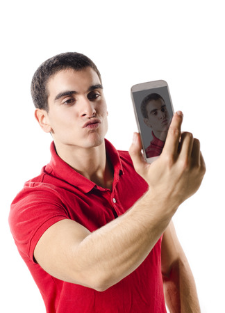 latin man: Isolated young man making selfie portrait with smart phone on white background Stock Photo