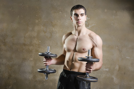 Young brunette man training shoulder muscles exercises in old gym wit dirty wall background photo