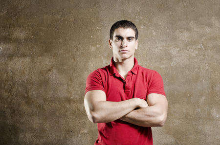 metrosexual: Young fit man posing on dirty wall background with crossed arms