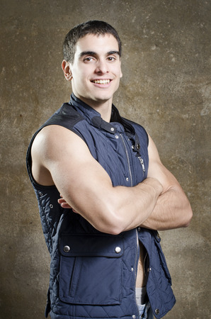 metrosexual: Posing strong young man with crossed arms on dirty wall background with sleeveless vest