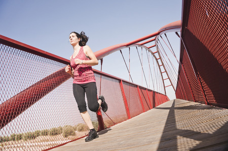 regular people: woman running on a footbridge to sunny day Stock Photo