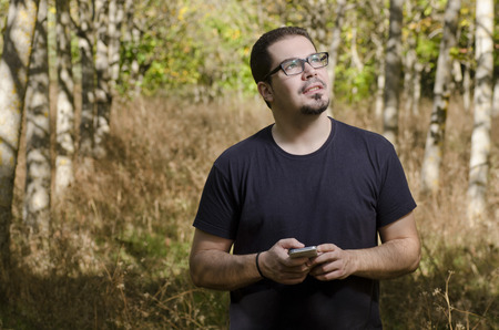 Scared regular searching telephone coverage alone in he forest photo