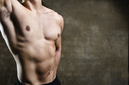 naked male body: Close up image of young man fitness gym torso with dramatic light on dirty wall background with copy space.