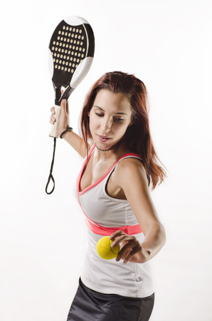 Young woman ready for paddle tennis serve on white background