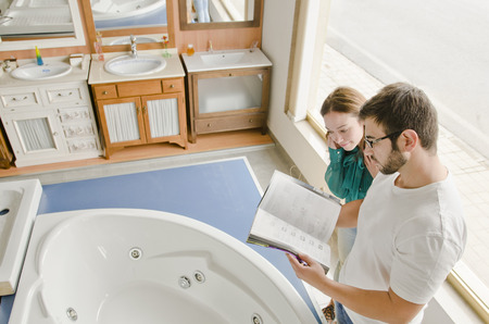 couple bathroom: Couple looking catalog in bath store near to the bahthub Stock Photo