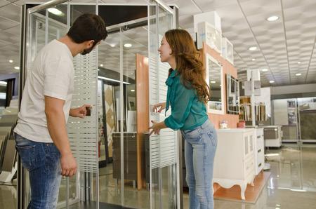 enclosures: Coppia al negozio di idraulico cercando cabine doccia e mobili.