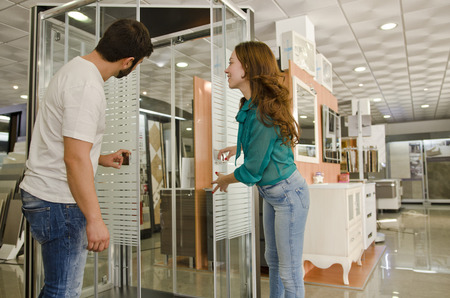 Couple at plumbing store looking shower enclosures and furniture.