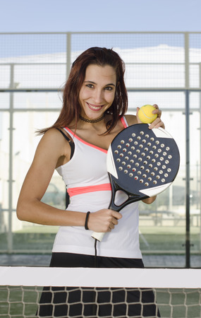 Paddle tennis woman player posing with racket and ball in outdoors court photo