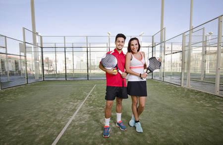 Paddle tennis couple posing in court in wide angle image