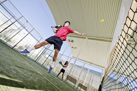 Paddle tennis couple playing in outdoors court. Wide angle image. Man hits ball. Stock Photo