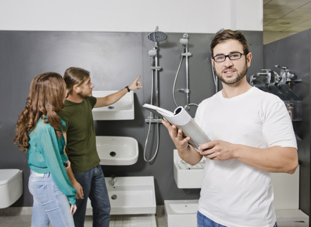 plumbing accessories: Sales clerk looking catalog at plumbing store with blurred couple looking in the background