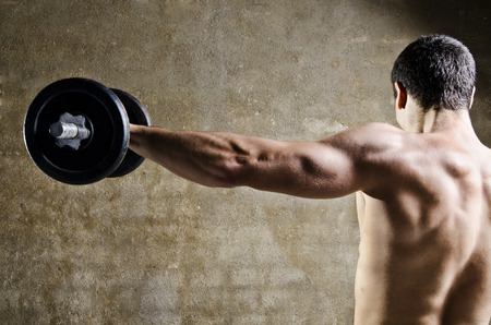 Closeup image of man lifting dumbbells in front of dirty wall background t old gym.