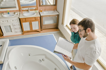 bath women: Couple looking catalog in bath store near to the jacuzzi bahthub Stock Photo