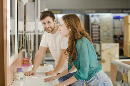 furniture store: woman and man in plumbing furniture store looking sink and mirror