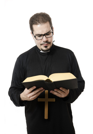 Isolated young priest reading the bible