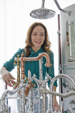 removals: Woman in faucets and plumbing store looking products and smiling