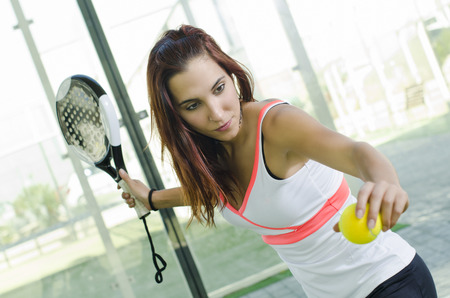 Attractive woman ready for paddle tennis serve