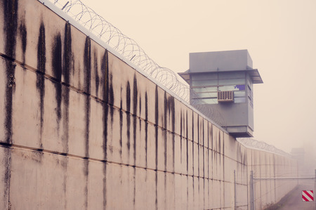 prison fence: Prison tower and wall in fog day