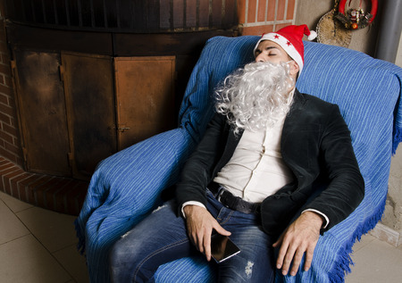 Young man with Santa Claus costume sleeping with possible hangover at sofa before christmas party photo