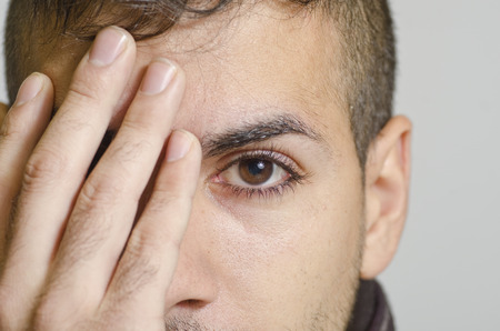 man face close up: Studio shot portrait of young man covering eye