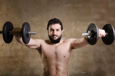 Adult spartan shirtless hipster man lifting weights photo